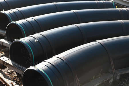 Large diameter black gasification pipes lie in a row in an open warehouse on the street on a summer day. 免版税图像