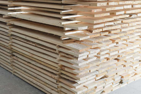 Wooden boards are stacked in a sawmill or carpentry shop. Drying and marketing of wood. 免版税图像