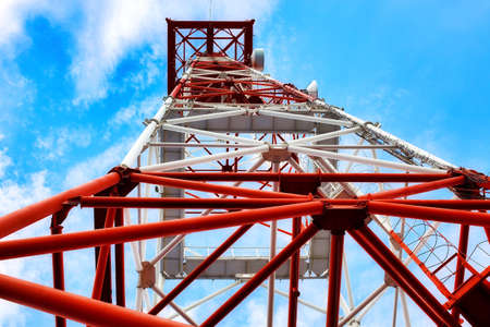 The communication tower stands against the sky with a bottom-up view.