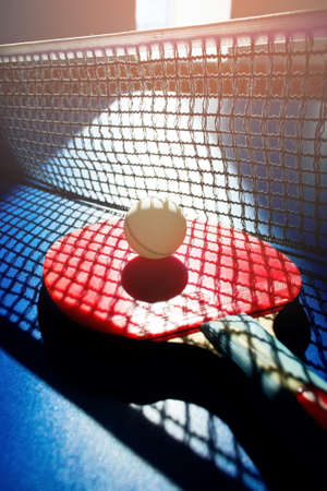 A red table tennis racket and a white ball lie on the surface of the table next to the net. Sports game