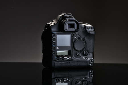 A black professional SLR camera sits on a glass table with a reflection. Rear view.