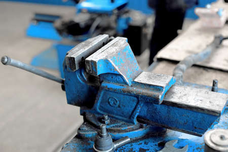 This is a large blue metal vise bolted to the workbench. An empty workplace in the workshop. 免版税图像
