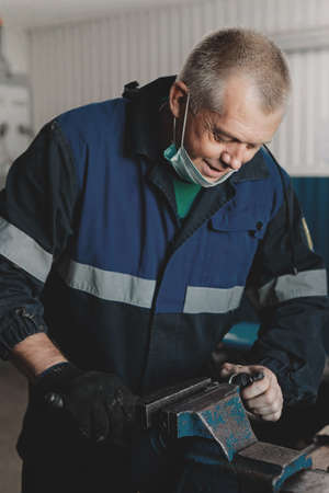 A white man in overalls is working in a room behind a workbench. A mechanic or locksmith clamps a metal part in a vise.