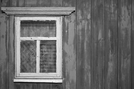 A wooden wall with an old rustic window. The concept of poverty and dilapidation.
