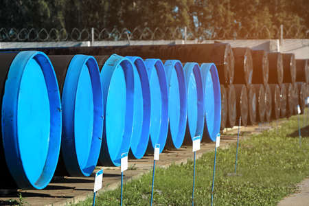 Large-diameter pipes with plugs lie in an open warehouse on a summer day. Storage and supply of gasification materials