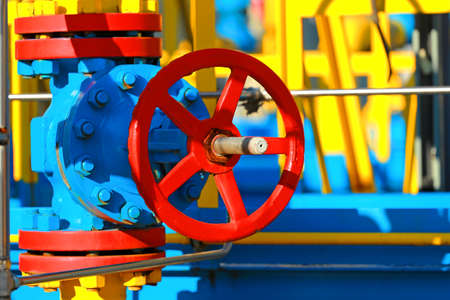 This is a red shut-off valve close-up on a sunny day in an open warehouse. Equipment for gasification