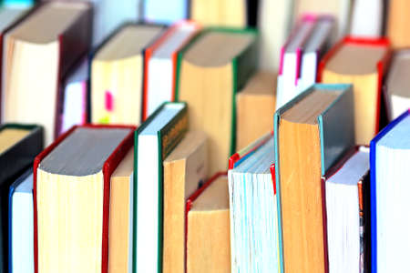 This is a lot of books standing together in several rows. Solid background of books in close-up.