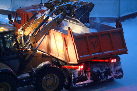 An excavator loads snow into the back of a dump truck at night. 免版税图像