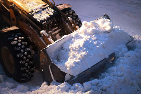 Excavator with a full bucket of snow. Snow removal from city streets at night. 免版税图像