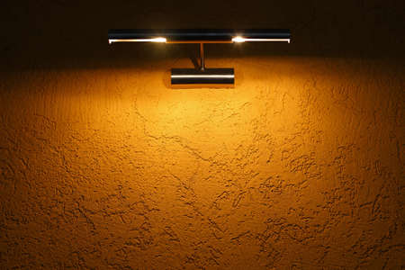 The yellow texture wall is illuminated by a light fixture on top.
