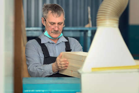 An elderly carpenter of Caucasian appearance works in a carpentry workshop. Processing of boards on a lathe.
