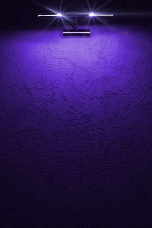 Blue vertical background for placing information. An empty texture wall with a light fixture on top.