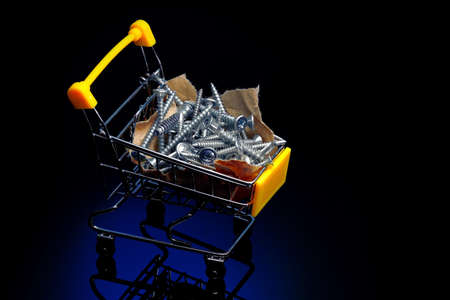 Steel screws lie on craft paper in a small shopping cart. Advertising photo for a supplier of fasteners