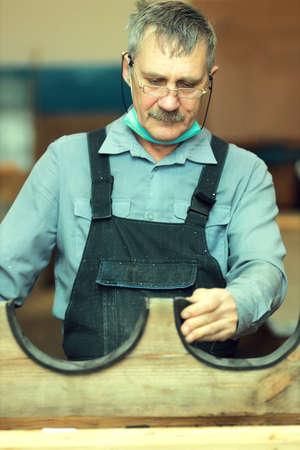 Portrait of an elderly carpenter in the workshop at work. 免版税图像