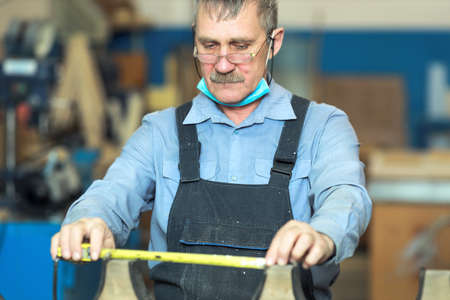 An old carpenter with a mustache and glasses is concentrating on his work. 免版税图像