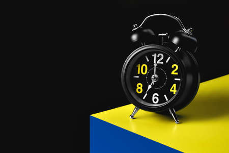 The hands of the alarm clock indicate seven oclock. A black alarm clock stands on the corner of a yellow-blue cube