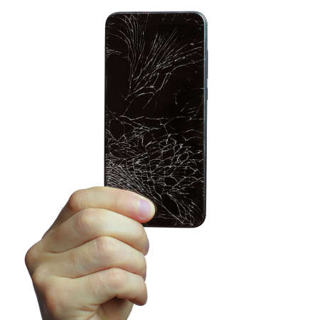 A mans hand holds a black phone with a broken screen. Isolated on a white background.