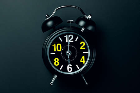A stylish black alarm clock with yellow and white numbers stands on a dark background. Blank for the designer