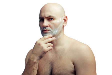 A bald white man prepares to shave his stubble. A mans face with shaving foam.