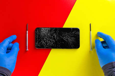 The gloved hands of a hardware repairman next to screwdrivers and a broken phone on a yellow-red background. Top view