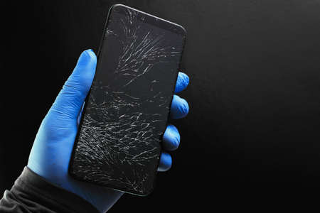 A broken touch phone with a cracked screen in your hand on a black background.