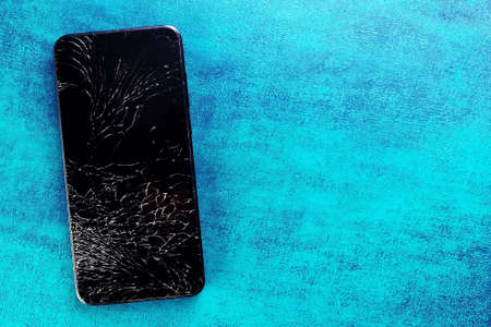A black phone with a broken screen lies on a turquoise textured background.