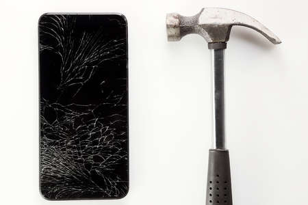 A broken black smartphone with a cracked display and a metal hammer lie on a white background.
