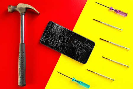 A black touchscreen phone with a cracked display next to screwdrivers and a hammer on a colorful bright background. 免版税图像