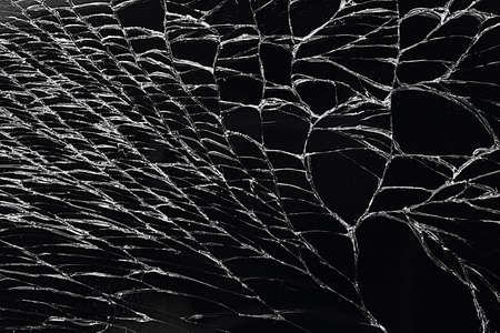 Broken glass display or cracked screen close-up. An empty, flat surface of black color.