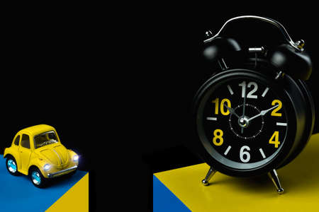 Toy cars and alarm clock on dark background with copy space