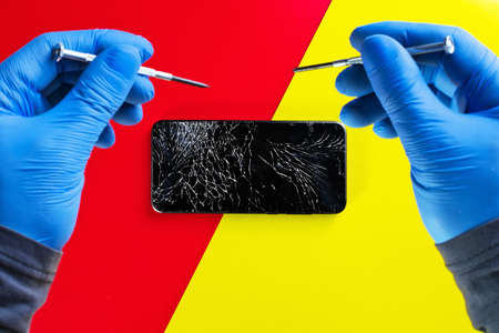 Repair of a cell phone.The hands of a master in gloves with screwdrivers over a broken smartphone with a cracked display