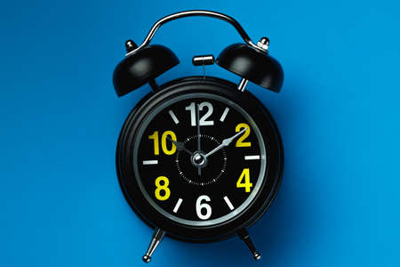A fashionable modern alarm clock in black with white and yellow numbers lies on a blue background.