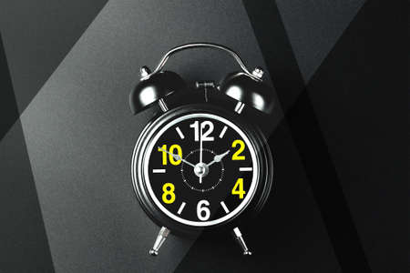 This is a stylish round alarm clock on metal legs on a dark background. A watch with large numbers on the dial