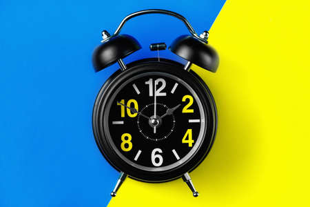 Black round metal alarm clock on legs on a bright composite background of blue and yellow color.