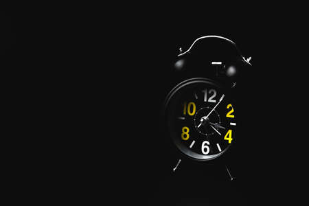Black round modern alarm clock on black background with copy space. The concept of insomnia and night anxiety