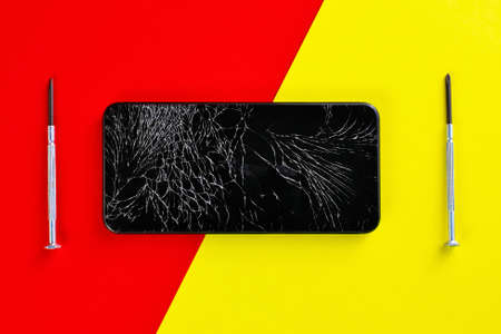A black smartphone with a cracked display and screwdrivers lies on a red and yellow background. Top view 免版税图像