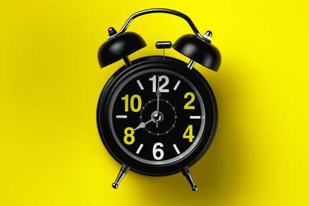 A black round alarm clock lies on a yellow background. Eight oclock before noon