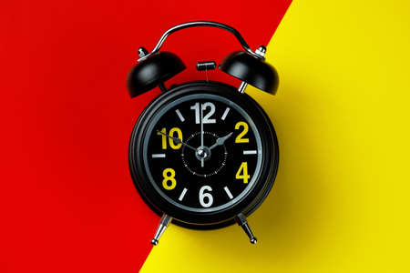 Black round metal alarm clock on legs on a bright composite background of red and yellow. Dial with large numerals.