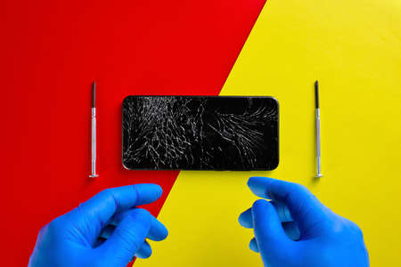 The phone with the broken screen lies on a red and yellow background with small screwdrivers and the hands of a master