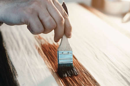 A working cabinetmaker holds a brush in his hand and paints a wooden surface. A trace of paint on a wooden board.