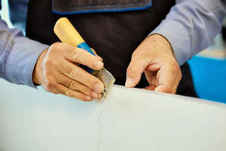 The hands of an elderly carpenter and a tool while working in close-up. Processing of a wooden plate with a cutter in a furniture shop. Close-up. working in a carpentry shop