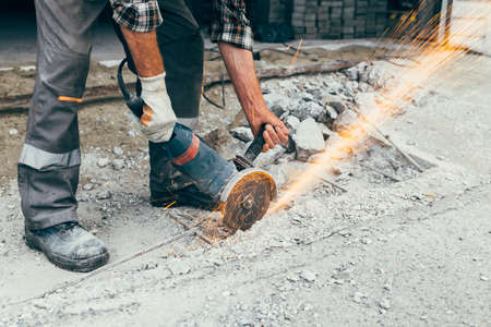 A worker with a grinder cuts the concrete pavement of the road and sparks fly. Construction and repair of the roadway. Foto de archivo