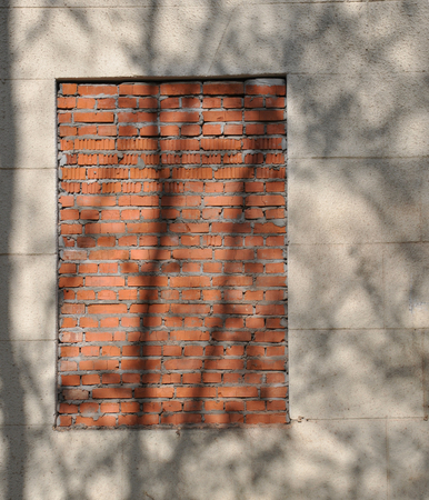 window shade: the window bricked up and the shade of the trees