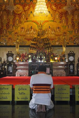 Thai person worshiping a Buddhist