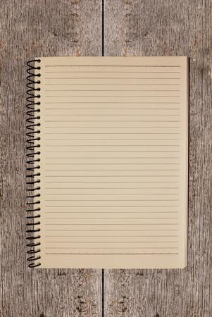 木製の背景に古いメモ帳
