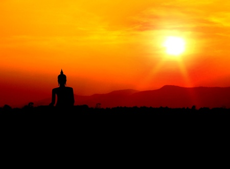 colorful sunrise: buddha silhouette  on mountain with sunset background