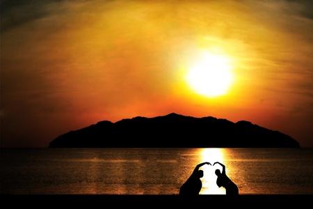 二人のシルエット夕日を背景にハートの形をしました。 写真素材