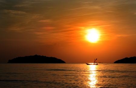 Silhouette of boat at sunset background