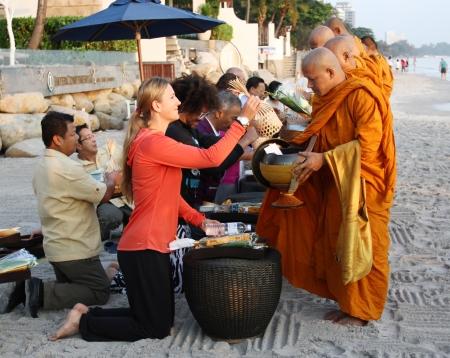 HUA HIN, THAILAND - DEC 28:Victoria Azarenka of Belarus gives food to a monks. Before tennis Match Hua hin World Tennis Invitation at Intercontinental resort on December 28, 2012 in Hua hin, Thailand.
