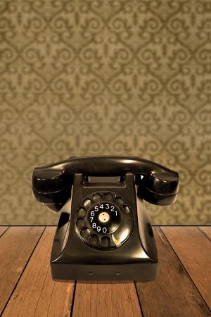 Retro telephone on vintage wallpaper photo